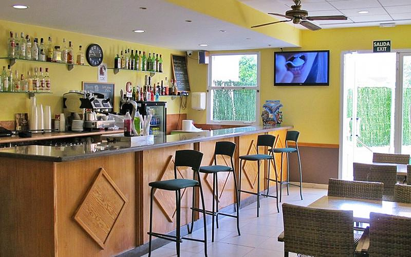 Four stools at the bar area with a large TV mouthed on the wall