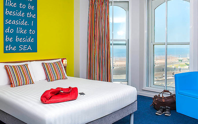 A white double bed in a yellow hotel room, featuring floor to ceiling windows and a bright blue chair