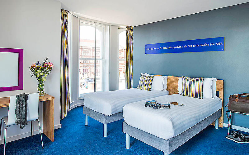 Two singles beds facing a desk in a blue hotel room