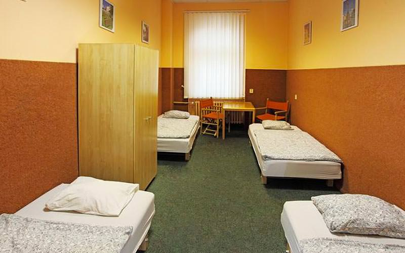 A room with four single beds and an orange colour scheme