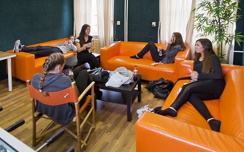 Some girls reclining on orange sofas in a communal area