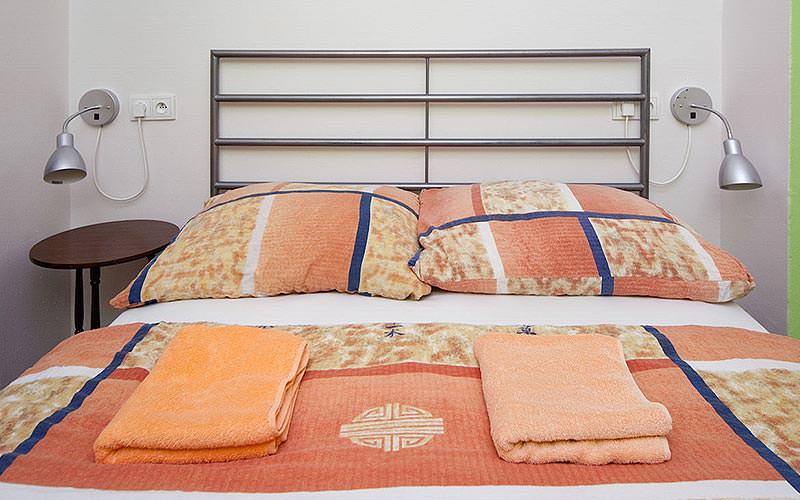 A double bed topped with an orange print cover, and folded up orange towels on top