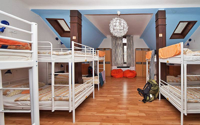 White bunk beds in a blue dorm room, with rucksacks and beanbags in the room