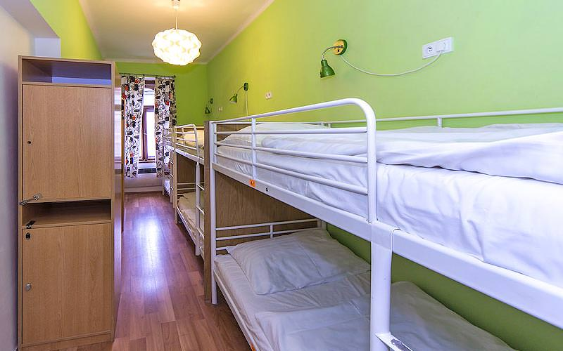 White bunk beds in a green hostel room, with cupboards along the wall