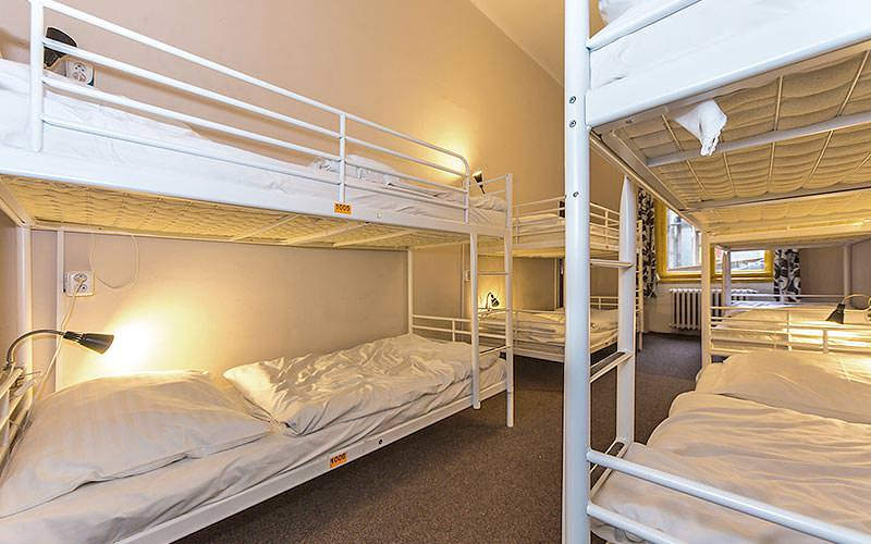 White bunk beds, featuring bedside lamps, in a dorm room