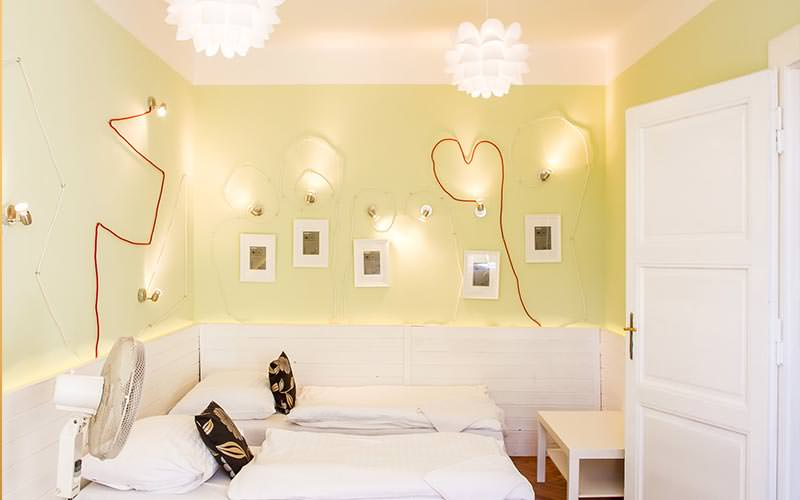 A double room with wires on the wall made into heart shapes