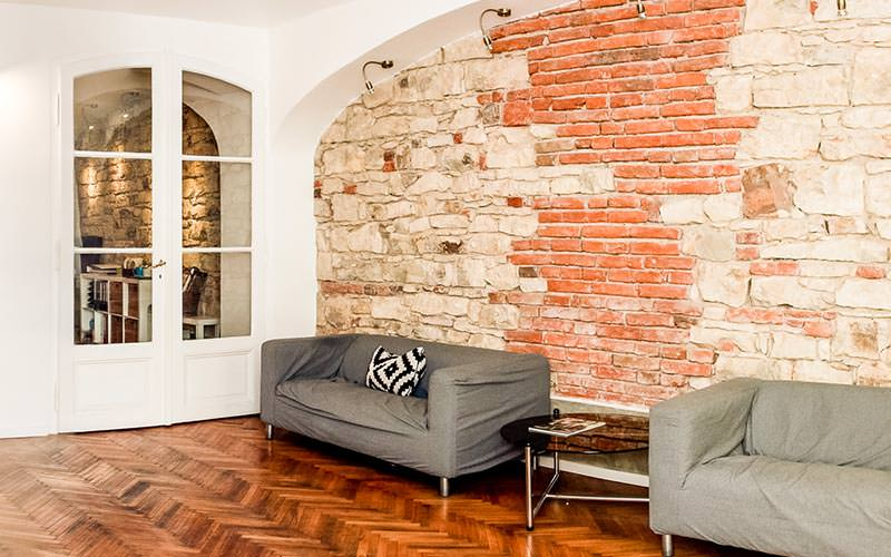 Exposed brickwork on the wall and two grey sofas in a room