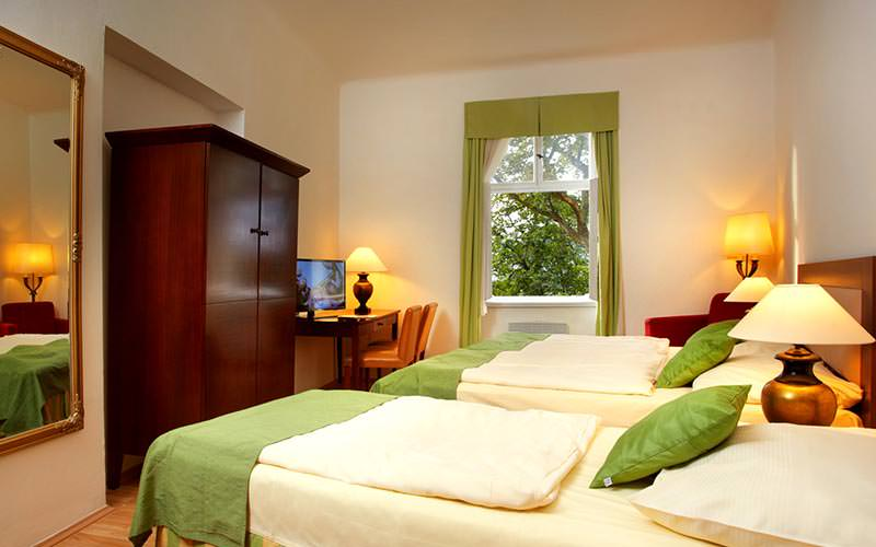 A room with a single and a double room in it, with a large dark wood wardrobe and a lime green and white colour scheme