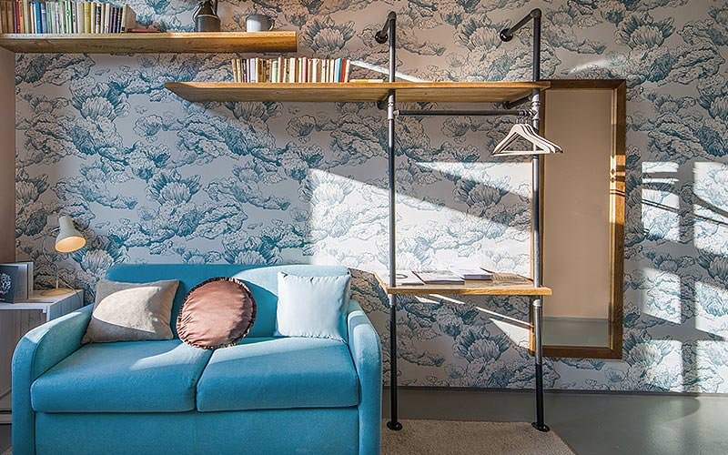 A blue, two seater sofa with shelves behind and brightly patterned wall paper