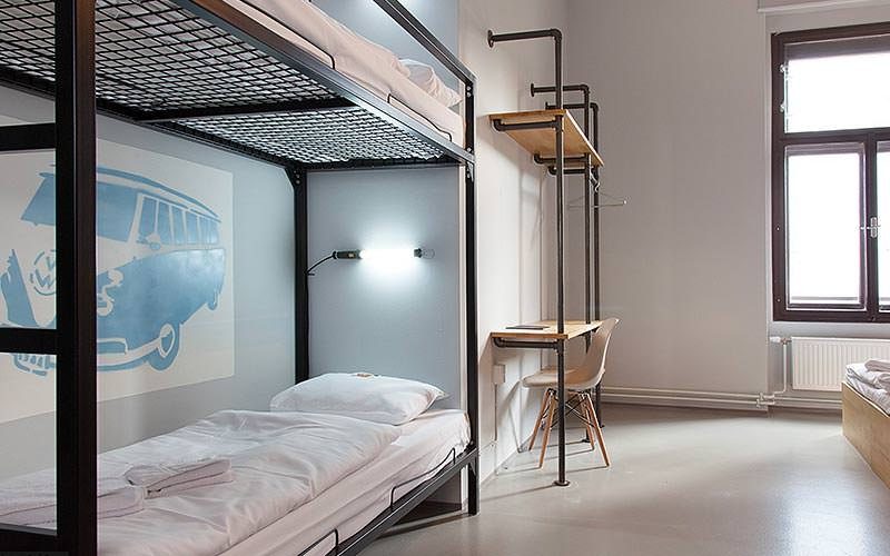 A bunk bed set into a wall, with a seating area at the back, and industrial style desk and shelf