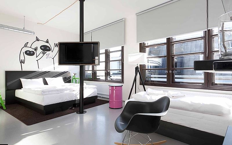 A large, modern double room with drawings on the wall and large windows lining the back wall