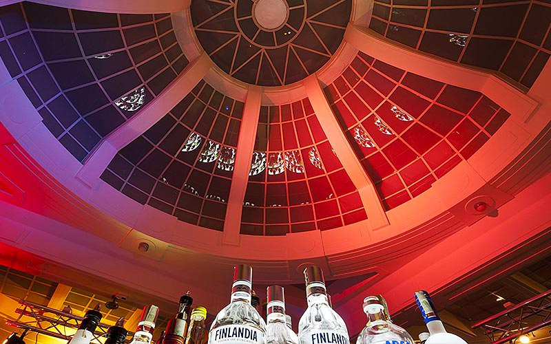 The ceiling of the bar with spirits illuminated in the foreground