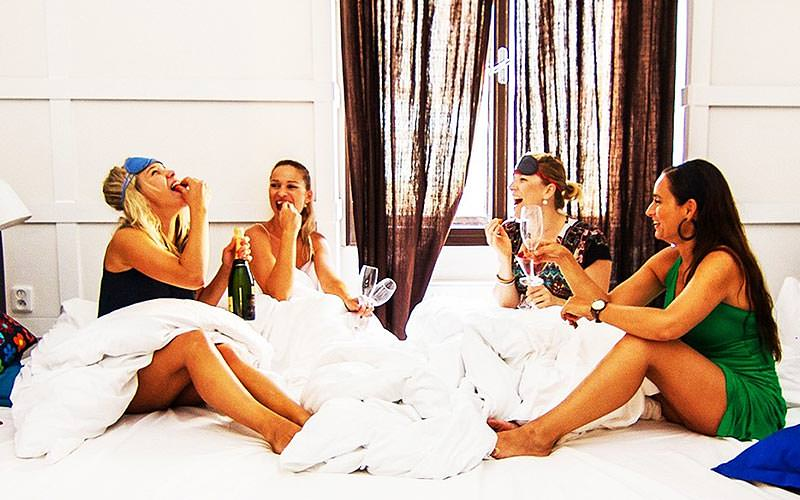 Four girls on a large bed, in their pyjamas with champagne flutes in their hands