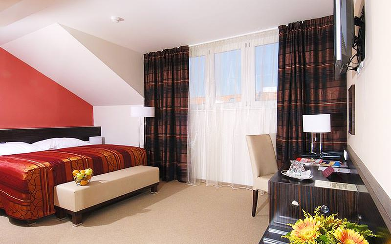 A large room with huge windows and a large double bed with red bedding