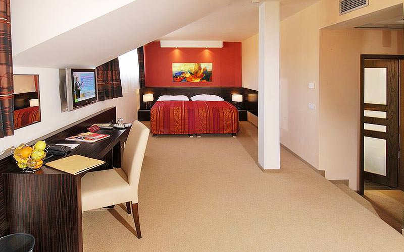 A large room with cream carpet, long desk and double bed in the background