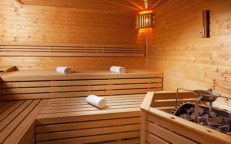 A wooden sauna, with a firepit in the foreground, and rolled up towels on the seats