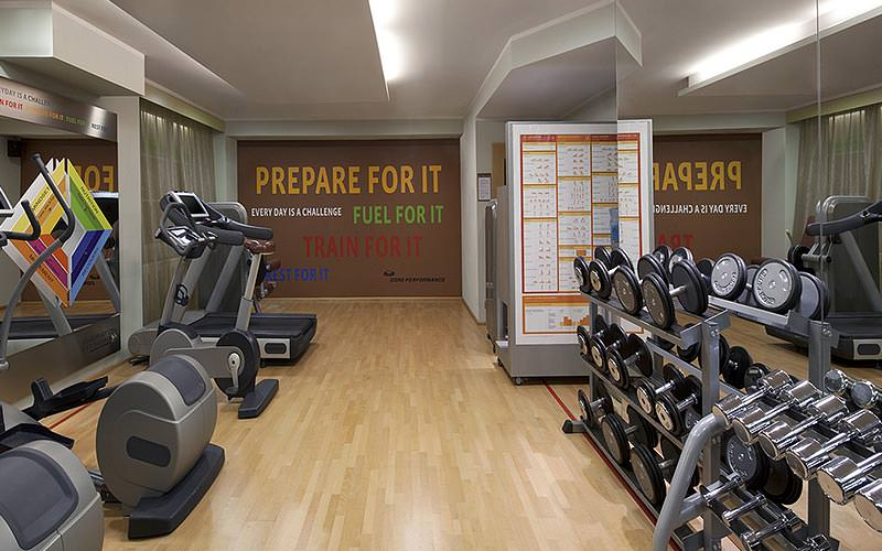 A gym with weights stacked in front of the mirror, and cross trainers on the other side