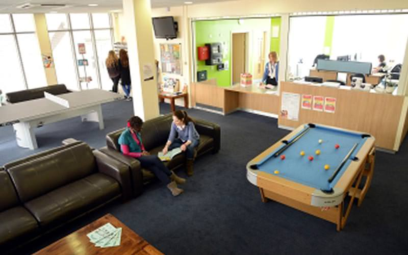 People sat on a black leather sofa in a games room, featuring a blue pool table and reception desk