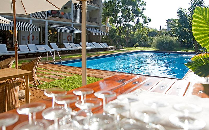 Glass stems on a table in the foreground, with sun loungers and an outdoor pool in the back