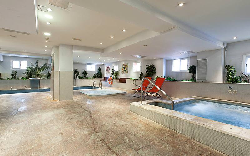 Indoor hot tubs and pool, with two orange deck chairs in the middle