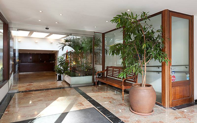 A lobby featuring a wooden bench and large plant pots