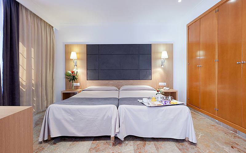 Two single beds with blue bedding, topped with a breakfast tray, with storage on the side and drawers in the foreground