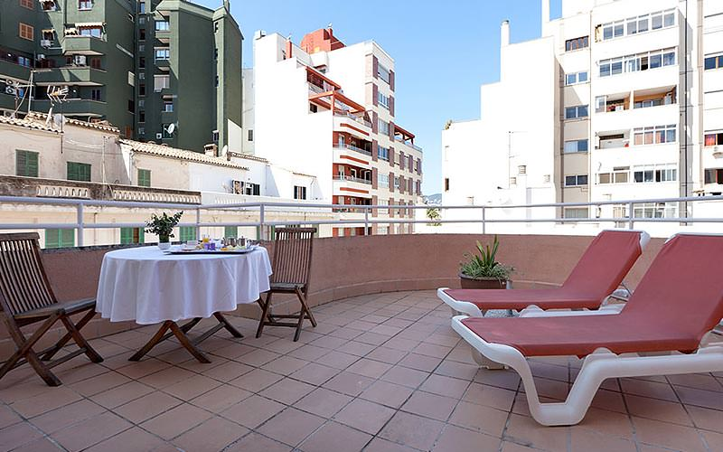 Two sunloungers and a table and chairs on a terrace, with buildings in the background