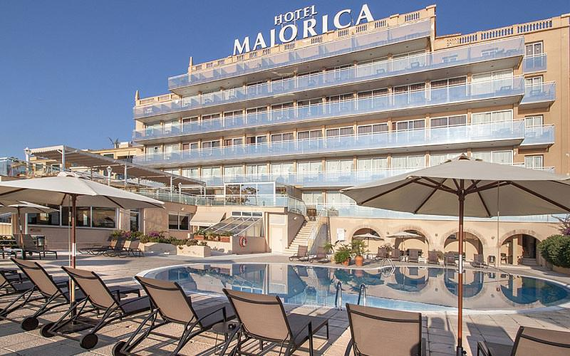 The exterior of Hotel Catalonia Majorica with a modern swimming pool and sun beds outside
