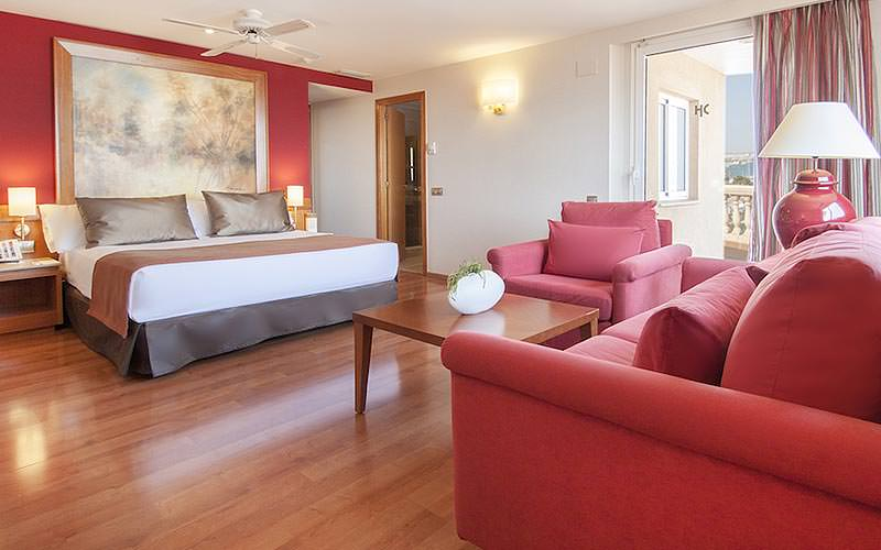A spacious double room with red sofa armchairs and a painting above the beds