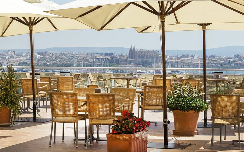 Lots of empty seats and parasols overlooking the city of Palma