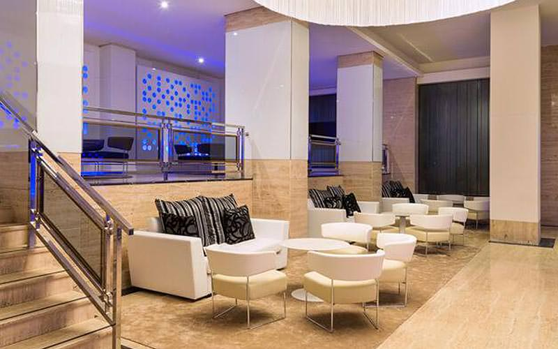 White seats and tables in the lobby area of Hotel Melia TRYP Bellver