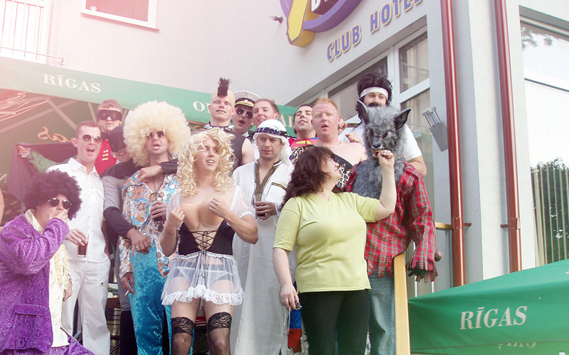 A group of men dressed in various costumes standing outside of a hotel