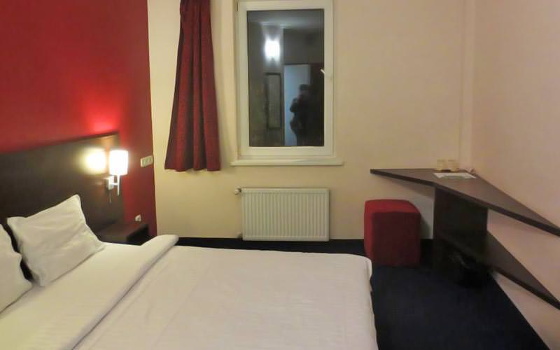 A white double bed in a red hotel room, facing a red stool and desk in the corner of the room