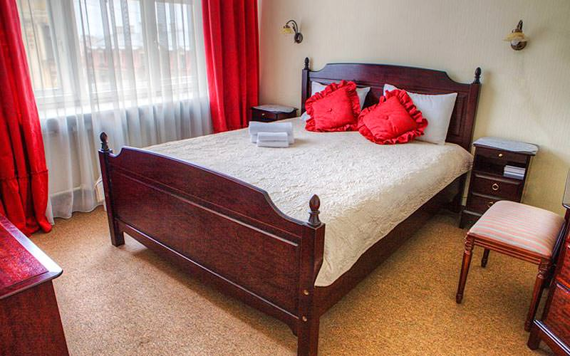 A wooden double bed topped with red cushions and a cream cover, with a bedside table and stool on the side