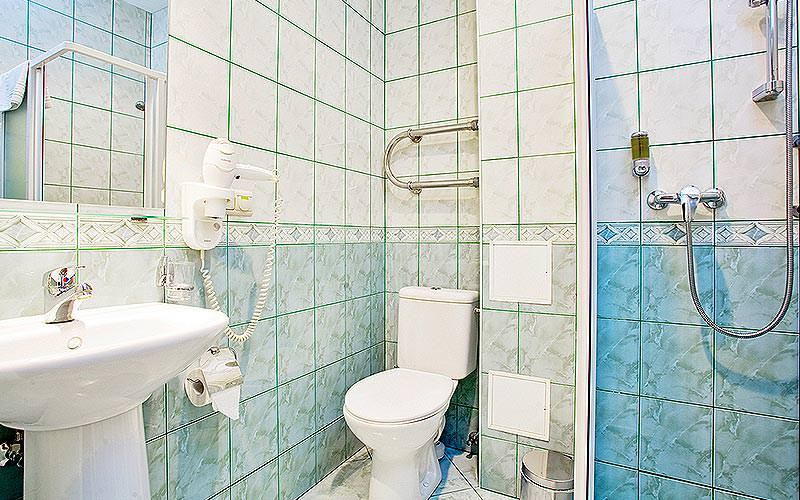 A blue and white tiled bathroom, with a sink, toilet and shower