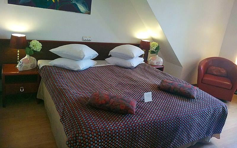 A double room in A1 Hotel with white walls and maroon bedding