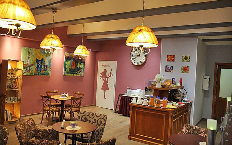 The cafe area in Hotel A1, with lots of quirky motifs on the wall, atmospheric lighting and different seating areas
