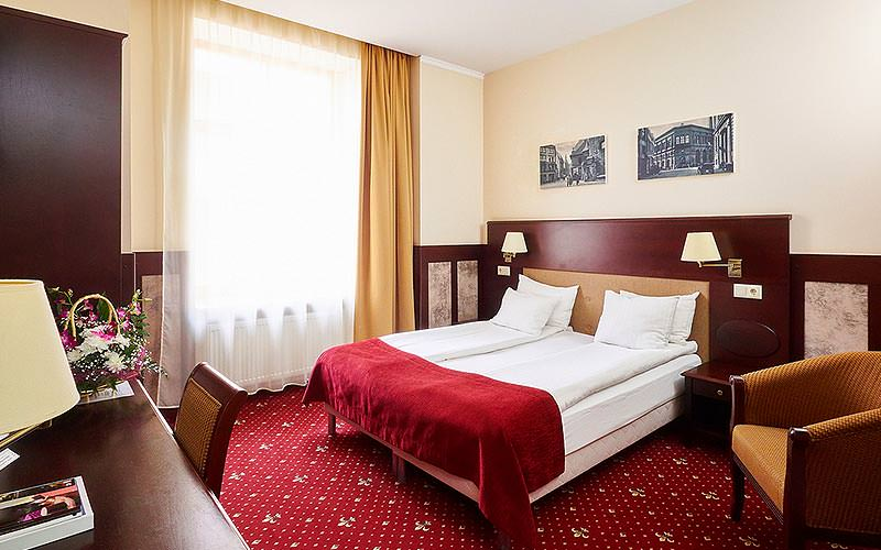 A double room with a red and gold colour scheme