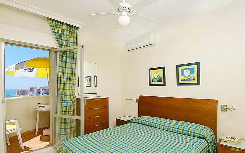 A bedroom of a CLC Benal Beach apartment with a balcony