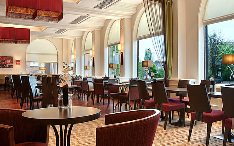 Tables and chairs in the hotel restaurant, featuring arched windows, at the Hilton York