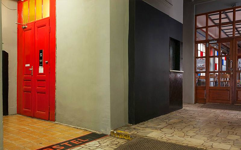 The lobby of Hostel Fleda, with a red door in the corner and brown doors in the other
