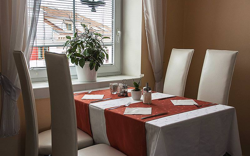 A table set for dinner with four cream chairs, adjacent to a window