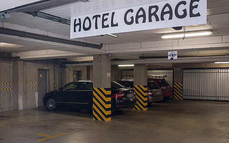 The Hotel Omega garage with three cars parked