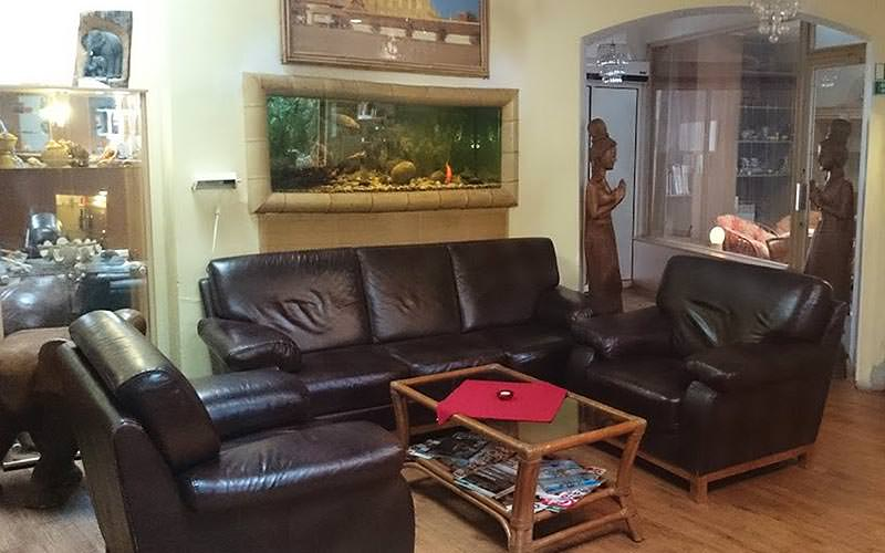 A leather brown sofa and two chairs around a glass coffee table in a room, with a fish tank in the wall in the back