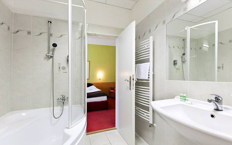 A bathroom within Hotel Slovan, with a shower, sink and towel rack