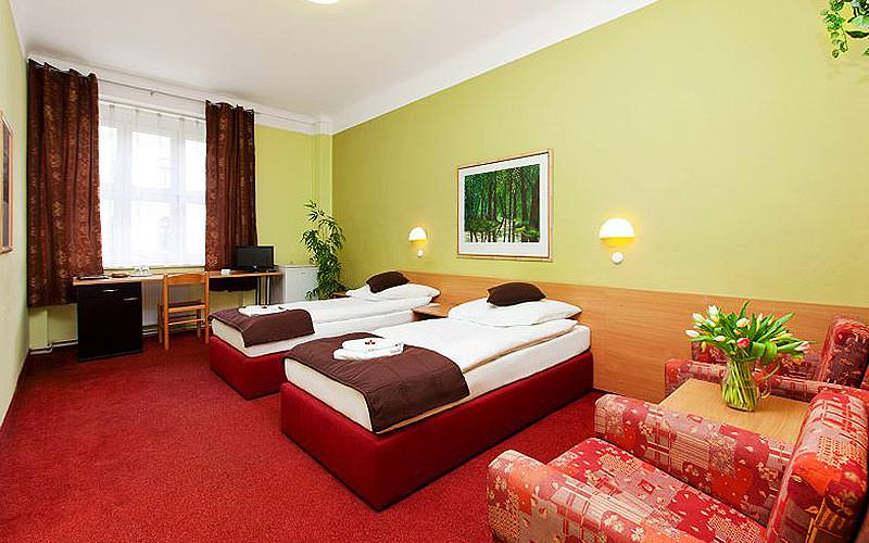 A twin room within Hotel Slovan, with lime green walls and a red carpeth