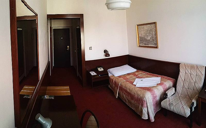 A single room in Hotel Slavia, with a single bed and an arm chair
