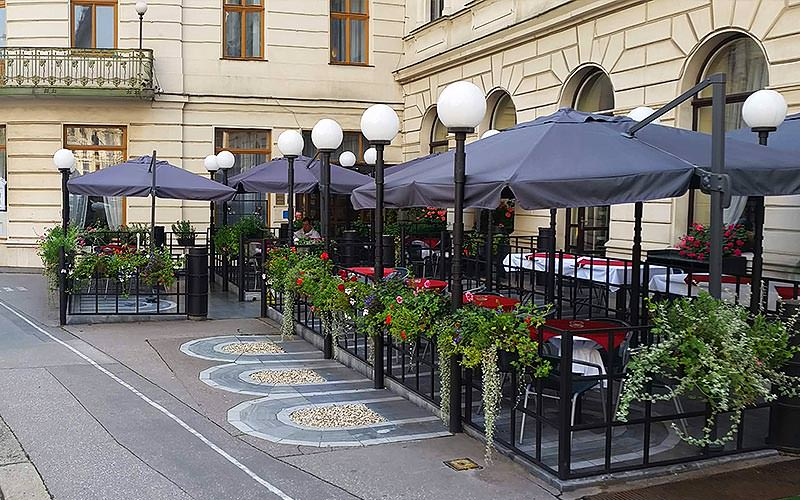 An outdoor seating area in Hotel Slavia, with black umbrellas and lighting