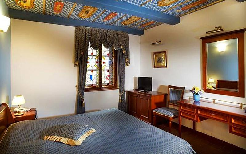 A small double room with blue bedding, a stained glass window and an ornate ceiling