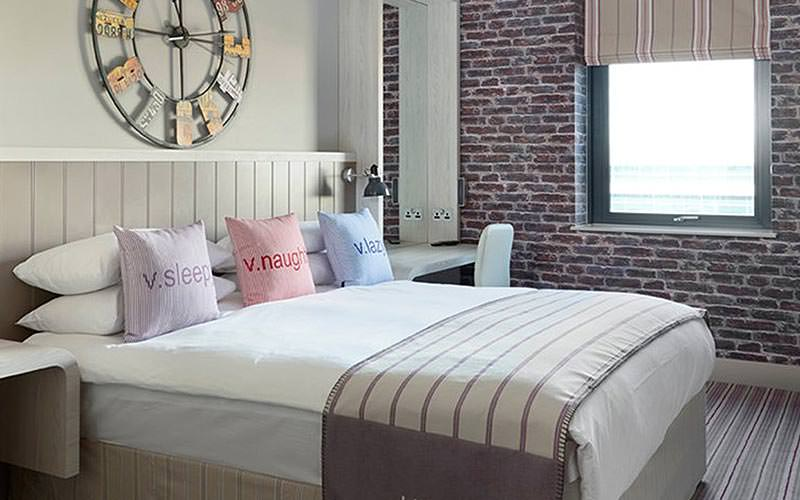 A double bed topped with cushions in an exposed brick hotel room